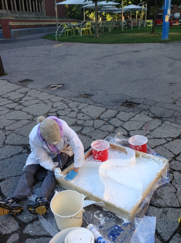 View of artist casting cracked sidewalk near Harvard University Science Center.